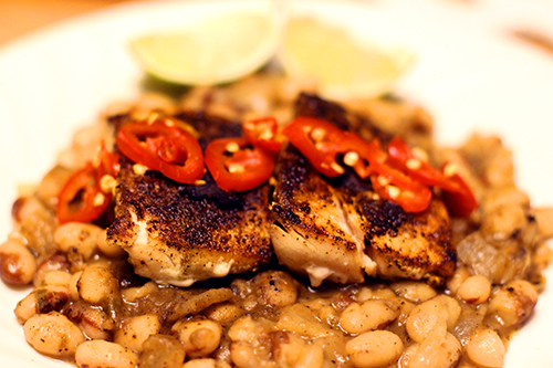 A plate of grilled mahimahi with beans and sliced jalepinos